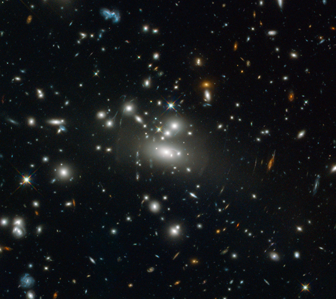 A bright lens of galaxies in the center warps and distorts more distant galaxies like ripples in space