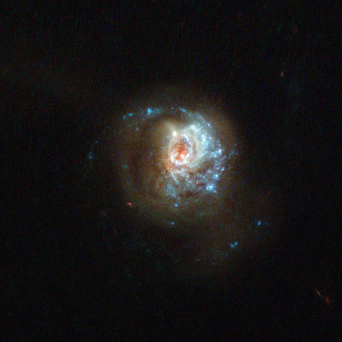 A hazy disk of millions of stars, with an off-center red/white core and brilliant sparkling blue arms stretching out from the bottom, around to the right and trailing up over the top, off into space