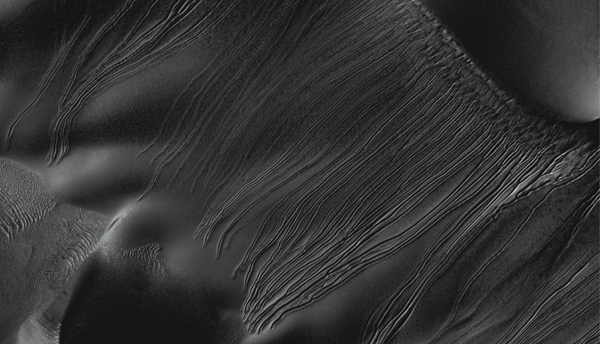 Several types of downhill flow features have been observed on Mars. This image from the High Resolution Imaging Science Experiment (HiRISE) camera on NASA's Mars Reconnaissance Orbiter is an example of a type called 'linear gullies.'
