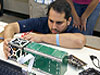 Students work with a cubesat during mission preps.