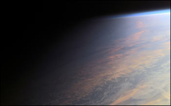 PHOTOGRAPH TAKEN FROM INTERNATIONAL SPACE STATION SHOWS HIGH CLOUDS TINTED WARM PASTEL COLORS BY THE SETTING SUN