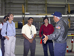 Pilot Dick Ewers describes flight research to visiting astronauts.