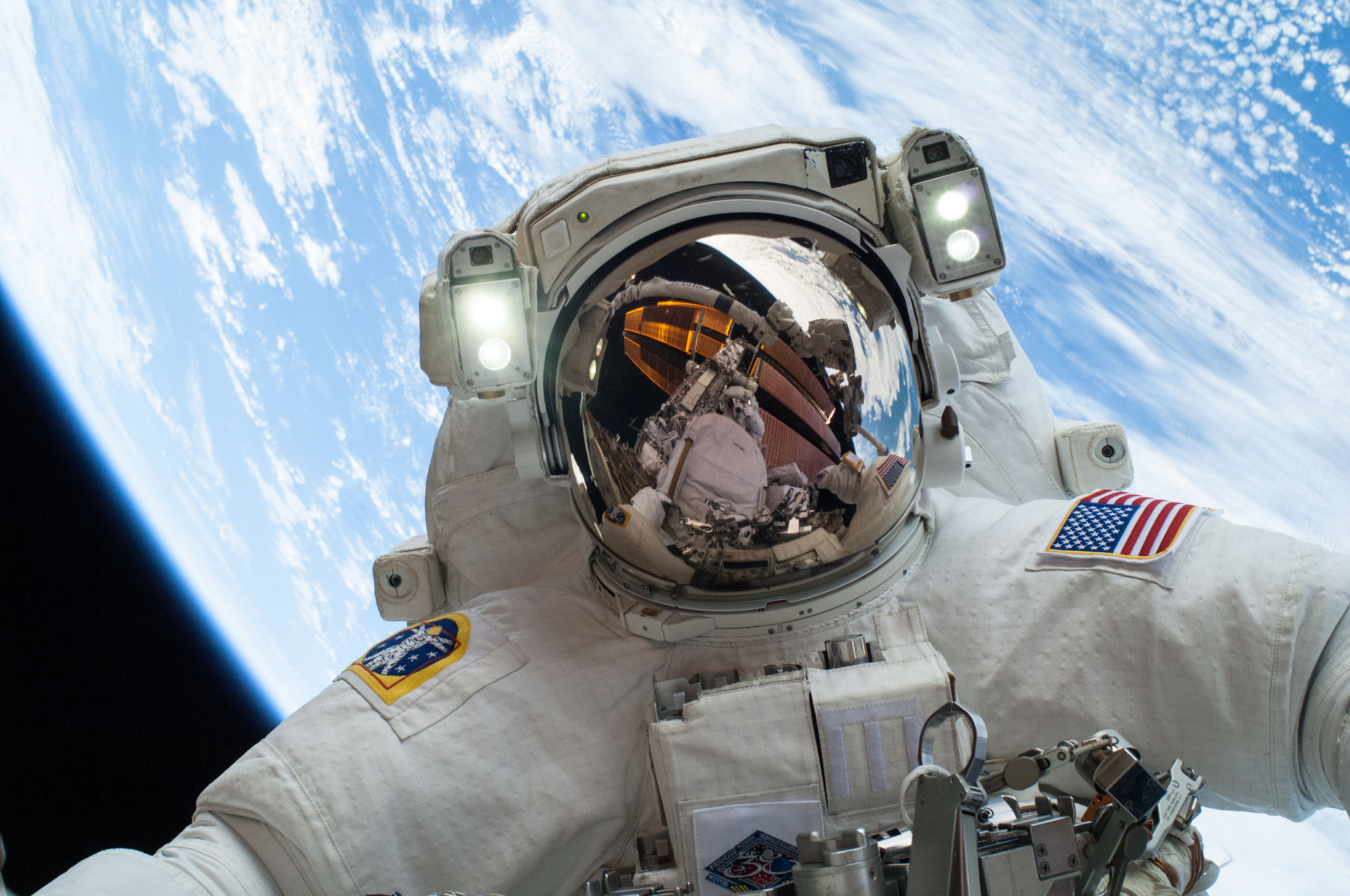 NASA astronaut Mike Hopkins participates in the second of two spacewalks, which were designed to allow the crew to change out a faulty water pump on the exterior of the space station. Fellow spacewalker Rick Mastracchio appears in the reflection of Hopkins' helmet. Image Credit: NASA