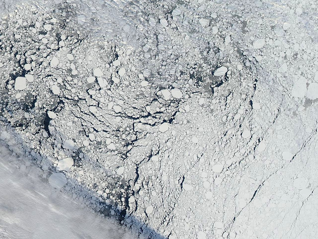 An image of an area of the Arctic sea ice pack well north of Alaska, captured by the MODIS instrument on NASA's Aqua satellite on Sept. 13, 2013. A cloud front can be seen in the lower left, and dark areas indicate regions of open water between sea ice formations. Image Credit: Image courtesy NASA Worldview
