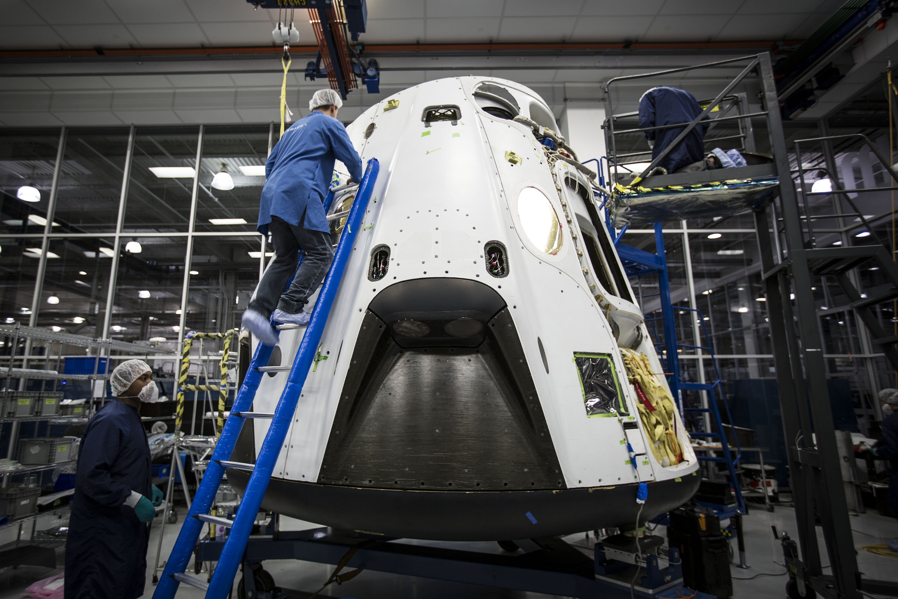 spacex dragon capsule inside facility with technician climbing ladder to top and second technician standing nearby