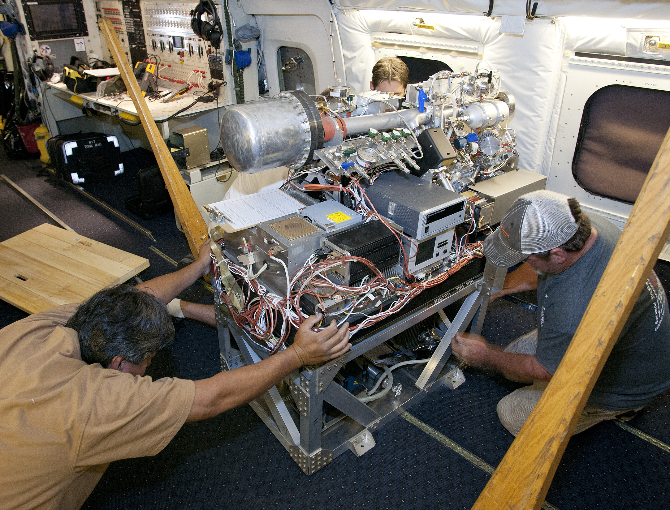Scientists and technicians ready an instrument rack for mounting in NASA's DC-8 flying laboratory in preparation for a complex mission to study how air pollution and natural emissions affect climate change. Image Credit: NASA / Tom Tschida