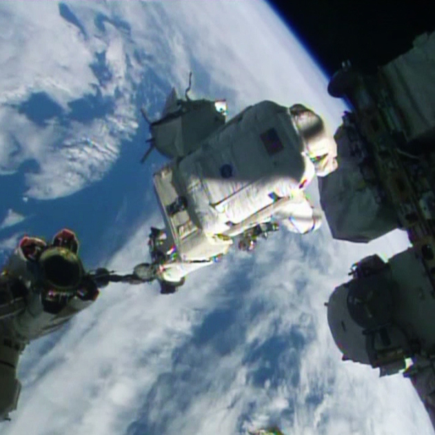 Spacewalker Alexander Gerst rides the Canadarm2 to a work site on the International Space Station.