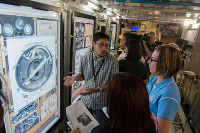 "Vincent Vidaurri, center, a technical specialist with Teledyne Brown Engineering supporting Mission Operations at the Marshall Space Flight Center, provides details about a mock-up of the International Space Station science lab to a group of area teachers as part of ""Back-2-School Day."""