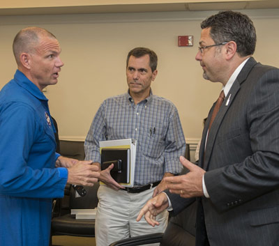 From left, Anthony Antonelli, a NASA astronaut and SLS Program PDR board crew office representative, talks with Tony Lavoie, manager of the Stages Office, and Todd May, manager of the SLS Program, after signing the preliminary design review completion certificate.