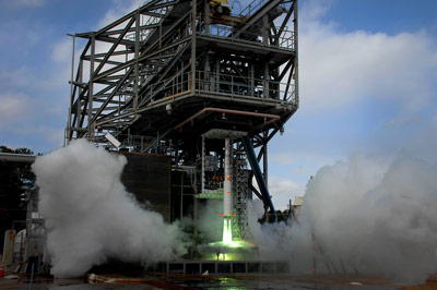 : A 5-percent scale model of the Space Launch System (SLS) is ignited for five seconds to measure the affect acoustic noise and pressure have on the vehicle at liftoff. The green flame is a result of the ignition fluid that is burned along with the propellant during this short-duration test.