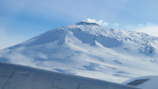 Antarctic volcano Mount Erebus seen over the NASA P-3's right wing during the landing approach.