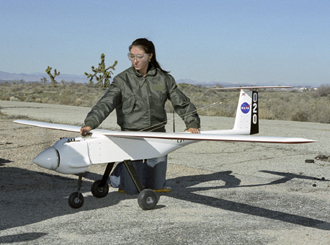 NASA Dryden Operations co-op student Shannon Kolensky holds one of the APV-3 UAVs.