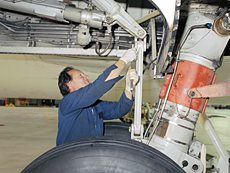 Asst. crew chief works on Guppy landing gear.