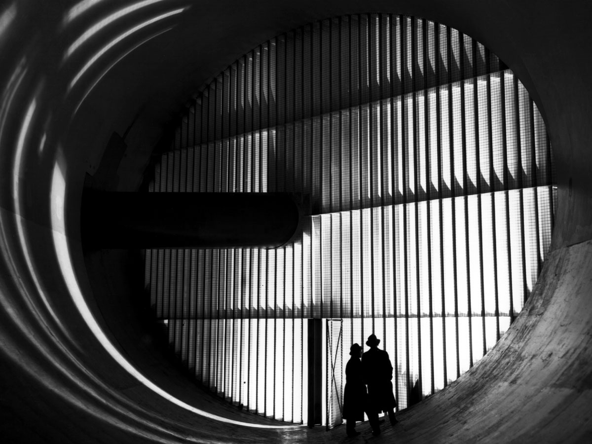 Black and white photograph of large end of wind tunnel with vertical slats running across and