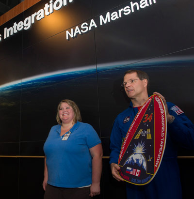 Expedition 34 Commander Kevin Ford, right, and Jenna Ruddock, an operations lead for several payloads in the Training and Crew Operations Branch of the Engineering Directorate at the Marshall Space Flight Center, prepare to hang the Expedition 34 mission plaque.