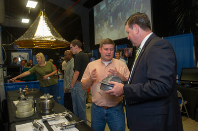 Marshall Center Director Patrick Scheuermann, right, discusses the finer points of using additive manufacturing to build engine parts with David Eddleman, a component engineer with the Engineering Directorate, during Innovation & Technology Day.