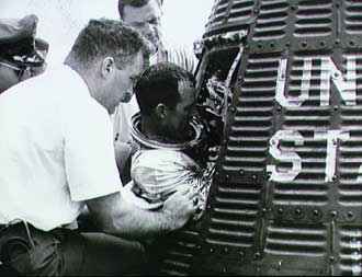 Gordon Cooper is helped from his Mercury capsule after recovery.