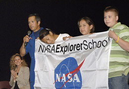 Former astronaut John Herrington presents students at Sanders Middle School with an Explorer School flag.