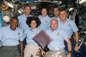 A large plastic container of basil seeds is shown floating in front of the crew of STS-118. The astronauts are Alvin Drew, Barbara Morgan, Scott Kelly, Charlie Hobaugh, Tracy Caldwell, Rick Mastracchio and Dave Williams.