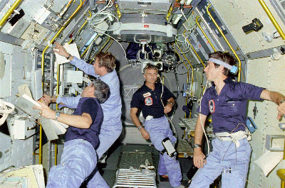 Aboard Spacelab 1 during STS-9 in 1983 are, from left, Mission Specialist Robert Parker, Payload Specialist Byron Lichtenberg, Mission Specialist Owen Garriott and Payload Specialist Ulf Merbold.