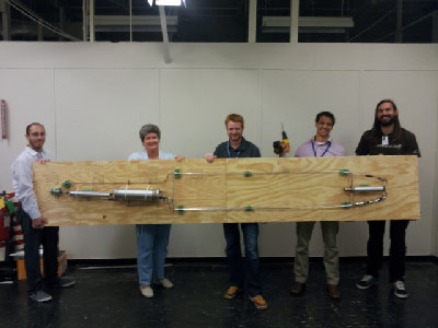 A display of Robert Goddard's famous rocket assembled by Marshall interns, from left, Carolos Mendoza, intern from Texas A&M University; Becky Farr, Marshall systems engineer and intern mentor; Cameron McCarty, intern from Columbus State University; Ryan Hatton, intern from Virginia Tech; and Chris Tellesbo, intern from the University of Utah.