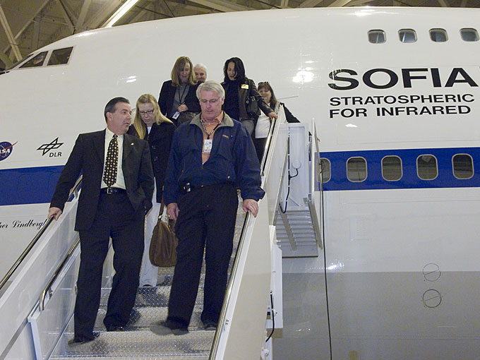 Mayor James Ledford of Palmdale, Calif., and Steven Schmidt, director of the Dryden Aircraft Operations Facility, lead a group of Palmdale civic officials down the stairs after a tour of the SOFIA airborne observatory.