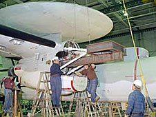Technicians at NASA Dryden's flight loads lab install a fixture inside an engine nacelle in preparation for major structural loads tests on an E-2C Hawkeye.