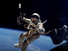 Astronaut Ed White wears a spacesuit while floating in space connected to the spacecraft by a tether