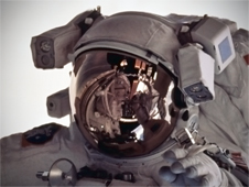 A spacesuit helmet with the gold visor down