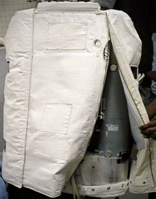 Cloth covering the Primary Life Support Subsystem unzipped to reveal an oxygen tank