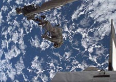 Astronaut Piers Sellers attached to the end of the shuttle's robotic arm high above Earth