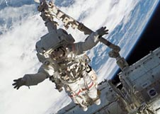 Astronaut Rick Linnehan works in space attached to Canadarm2