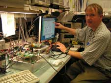 NASA Goddard engineer Dave Fisher testing the channel coder implemented in a communication subsystem in a lab.