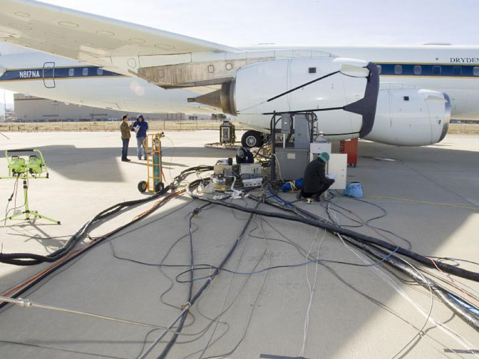 A maze of wires and tubing to connect data-collection instrumentation to the control centers is laid out on the pavement beside NASA's DC-8 flying laboratory