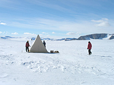 A white tent set up on a snowy landscape in Antarctica