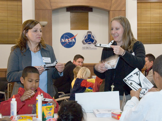 AERO Institute programs manager Kimberly Irizarry and education specialist Sara Cutts demonstrate how to assemble a paper cut-out space shuttle to children at the Family Night program at the AERO Institute