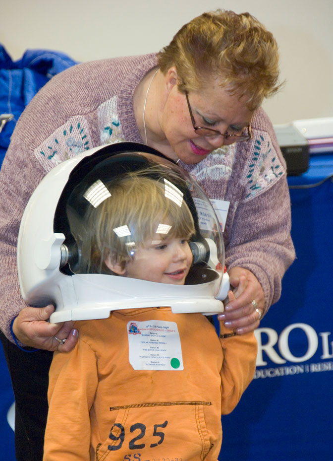 Micah Ericson finds the space helmet being fitted over his head by aerospace education spe-cialist Tibi Marin a tad large during the AERO Institute's Family Night program.