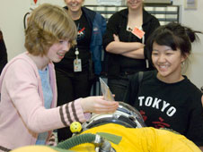 Phoebe Coy from Endeavour Middle School and Summer Ly from Del Sur School, both in Lan-caster, Calif., try their hand at inserting a feeding tube into the helmet of a pressure suit used by pilots of high-altitude aircraft during the Tech Trek tour of NASA Dryden Flight Research Center.