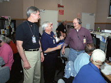 Kevin L. Petersen, center, talks with Griffin P. Corpening, right, X-43A chief engineer, while then Associate Administrator for Aeronautics J. Victor Lebacqz shares the moment.