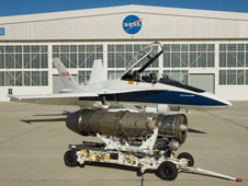 A twin-engine NASA Dryden F-18 support aircraft with a GE F-404 engine on display alongside.