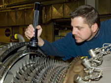 Jet engine mechanic Aaron Rumsey inspects compressor blades on a GE F-404 engine.