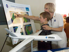 Dryden public affairs specialist Beth Hagenauer of Tybrin Corp. shows Branch Elementary School student Aubrey Knight areas where the Ikhana unmanned aircraft flew during infrared wildfire imaging missions in 2007.