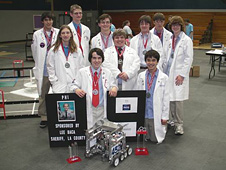 Members of the Power through Higher Innovation or PHI robotics team 452 gather around their mechanical masterpiece.