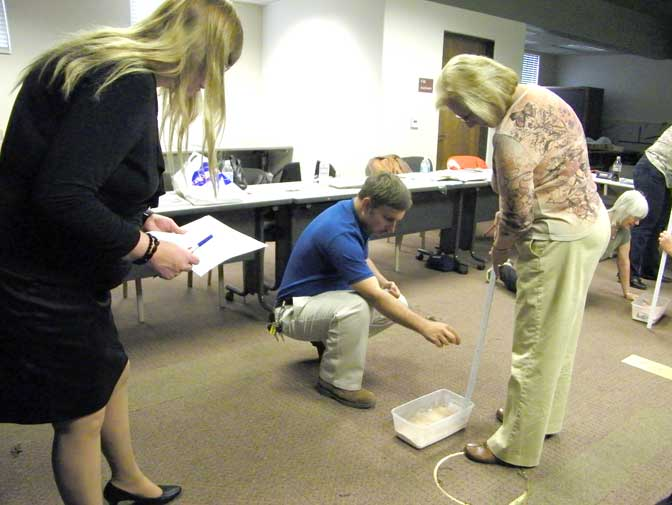 NASA Dryden historical archivist Peter Merlin assists two teachers in performing a simulation of tools used by astronauts during the Apollo missions to the moon 40 years ago.