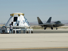 The Orion flight test crew module continues to undergo integration and testing of components. An Air Force Flight Test Center F-22 passed the test article.