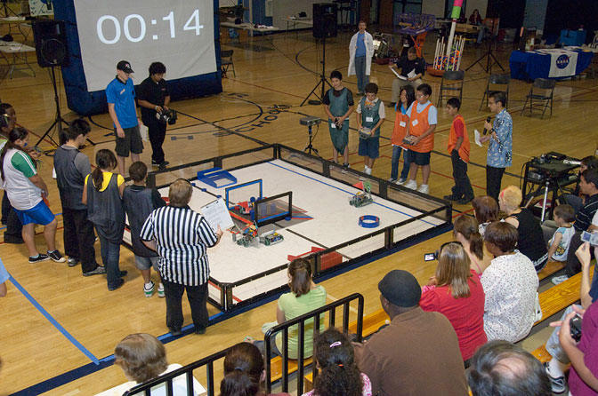 student teams maneuver their small robots around to pick up pucks and deposit them in a goal in their opponents' end zone.