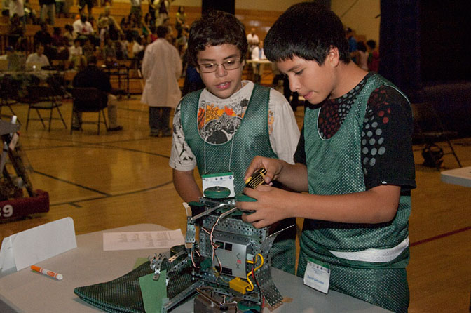 Saul Figueroa and Daniel Gonzalez work on their robot built during the middle school VEX robotics workshop.