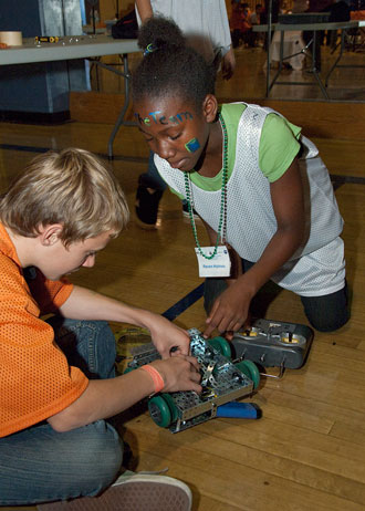 Raven Holmes gets help in fixing her VEX robot from a Lancaster High Eagle Robotics Team member as she gets ready for the Saturday morning competition