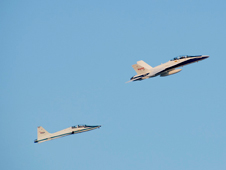 A Dryden F/A-18 and a T-38 fly over Clear Channel Stadium as part of the Lancaster JetHawks Aerospace Appreciation Night.