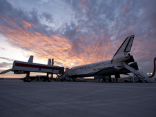 The Crew Transport Vehicle, where astronauts first go after a shuttle landing, is positioned for the Discovery crew to board as the sun sets on the high desert.